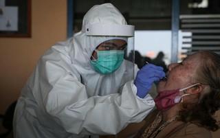 Ket Foto : Tim kesehatan khusus penanganan virus corona melakukan tes swab (CNN Indonesia.com)