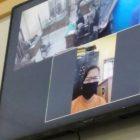 Ket Foto : Terdakwa Erdina Sembiring saat mendengarkan dakwaan melalui layar monitor.