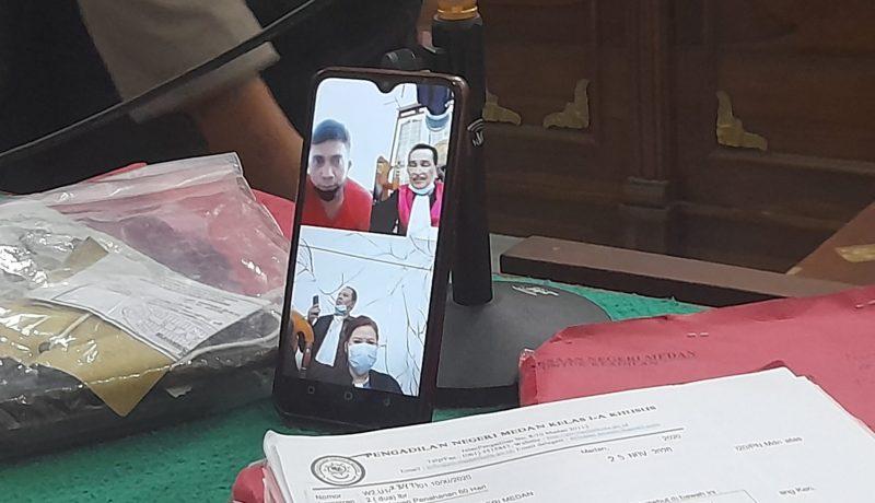 Ket Foto : Terdakwa Ade Saputra Ginting saat mendengar dakwaan JPU Sri Delyanti melalui video conference.