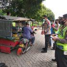 Ket Foto : Kapolsek Patumbak, Kompol Arfin Fahreza didampingi anggota membagikan nasi bungkus kepada penarik becak bermotor.